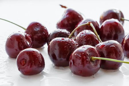 Fresh cherry berries with water drops on white background. Selective focus.