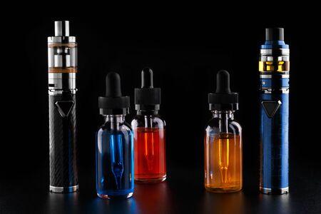 Elektronische sigaretten en flessen met vape-vloeistof op zwarte achtergrond Stockfoto