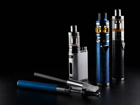electronic cigarettes or vaping devices on black background Foto de archivo