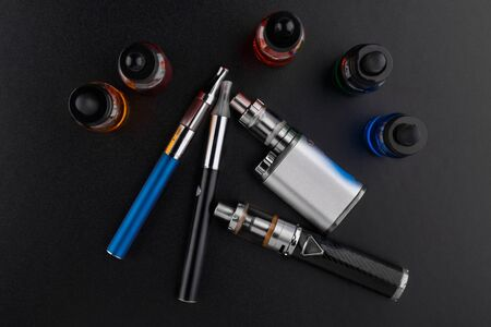 electronic cigarettes or vaping devices and bottles with vape liquid on dark background Reklamní fotografie