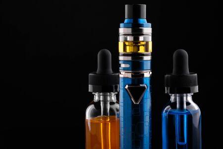 Electronic cigarette and bottles with vape liquid on black background Foto de archivo