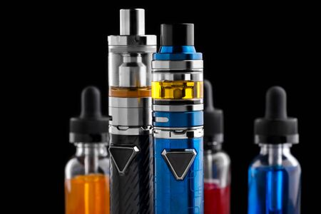 Electronic cigarettes and bottles with vape liquid on black background