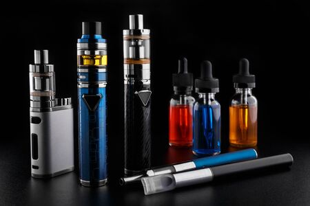 Electronic cigarettes and bottles with vape liquid on black background