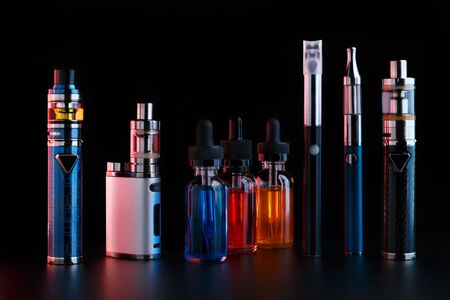 Electronic cigarettes and bottles with vape liquid on black background. Toned light Reklamní fotografie