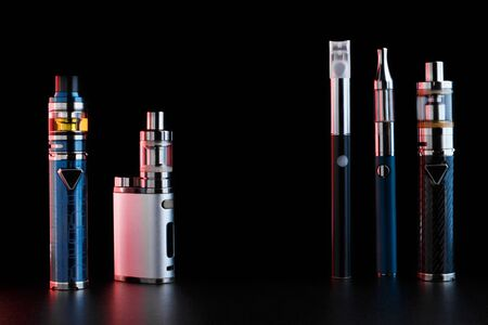 electronic cigarettes or vaping devices on black background. Toned light