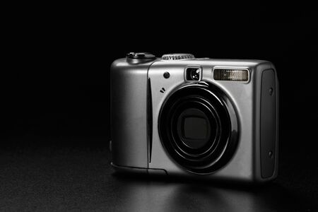 Compact amateur digital camera on black background