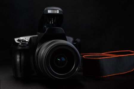Professional digital SLR camera with opened built-in flash on black background.