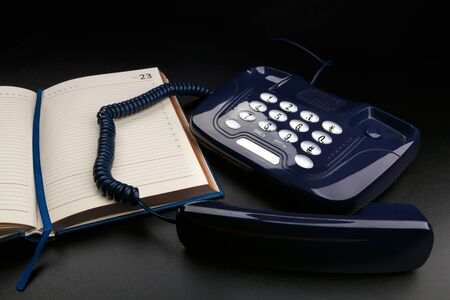 Outdated push-button telephone with handset and personal organizer on black background
