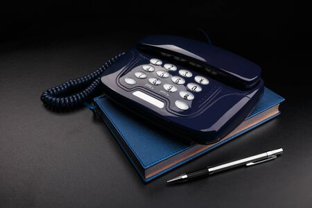 Outdated telephone with push buttons standing on personal organizer. Black background