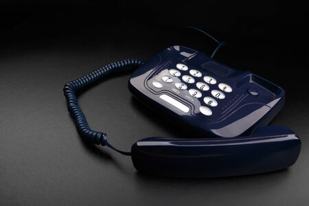Outdated push-button telephone with handset on black background