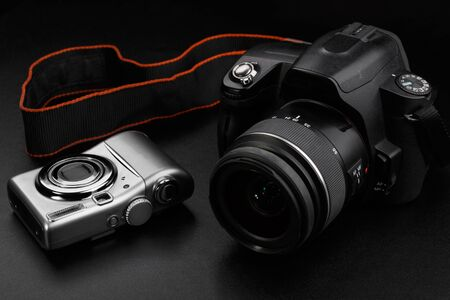 Compact amateur and professional dslr cameras on black background 写真素材