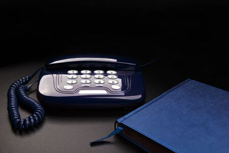 Outdated telephone with push buttons and personal organizer on black background