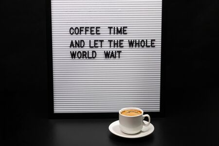 Cup of coffee and a letter board with inscription.