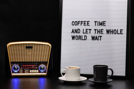Cups of coffee, radio receiver and letter board with inscription.