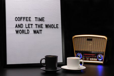 White and black cups of coffee, retro-styled radio receiver and letter board with inscription coffee time and let the whole world wait Foto de archivo