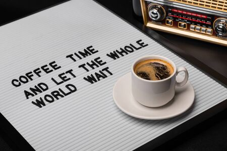 High angle view on cup of coffee and letter board with inscription.
