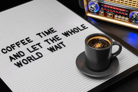 High angle view on black cup of coffee and letter board with inscription coffee time and let the whole world wait