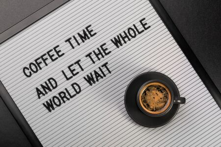 View from above on black cup of coffee and letter board with inscription coffee time and let the whole world wait