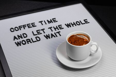 High angle view on white cup of coffee and letter board with inscription coffee time and let the whole world wait