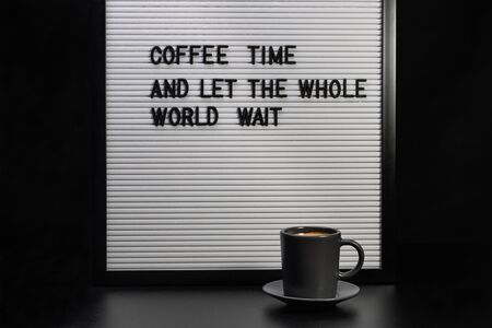 Black cup of coffee and letter board with inscription coffee time and let the whole world wait Foto de archivo