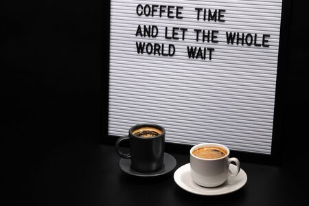 Black and white cups of coffee and letter board with inscription coffee time and let the whole world wait