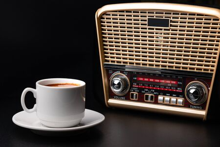 White cup of coffee and retro-styled radio receiver on black background