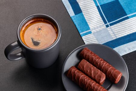 Cup of coffee and chocolates on dark background Foto de archivo - 137588956
