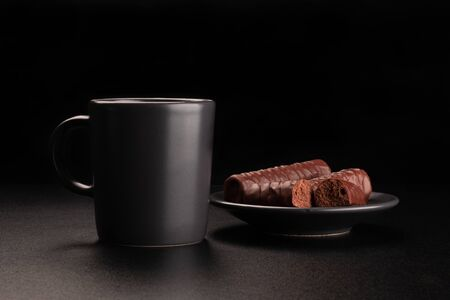 Cup of coffee and chocolates on saucer. Dark background Foto de archivo - 137586275