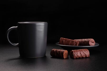Cup of coffee and chocolates on saucer. Dark background Foto de archivo