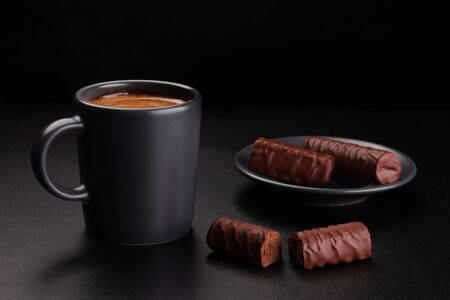 Cup of coffee and chocolates on saucer