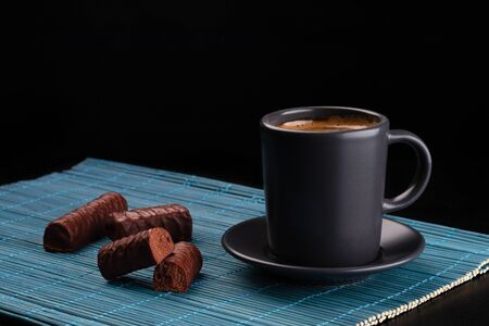 Cup of coffee and chocolates on bamboo mat Foto de archivo