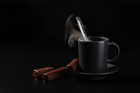 Cup of hot drink with spoon and chocolates on dark background