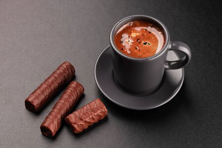 Cup of coffee and chocolates on dark background Foto de archivo - 137593137