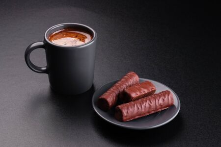 Cup of coffee and chocolates on dark background
