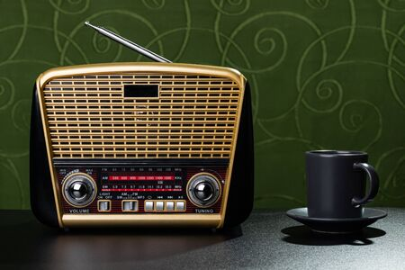 Radio receiver and cup of coffee on green fabric background