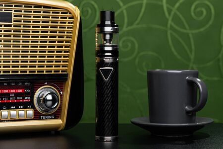 Radio receiver, cup of coffee and electronic cigarette on green fabric background