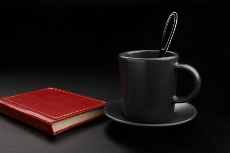 Cup of coffee with spoon and book on black background Foto de archivo