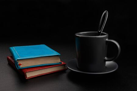 Cup of coffee with spoon and books on black background