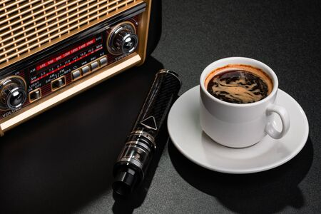 Radio receiver, cup of coffee and electronic cigarette on black surface
