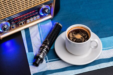 Radio receiver, cup of coffee and electronic cigarette on fabric napkin Foto de archivo