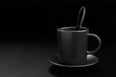 Coffee cup with spoon on black background