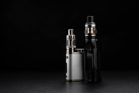 Electronic cigarettes or vaping devices on black Foto de archivo