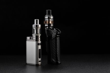 Electronic cigarettes or vaping devices on black Foto de archivo - 142117748