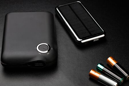 Powerbanks for charging mobile devices on black surface Foto de archivo