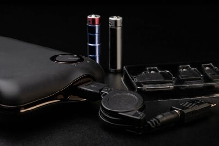 Powerbank for charging mobile devices and set of recharger heads on black background Foto de archivo