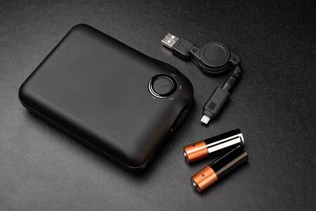 Powerbank for charging mobile devices on black surface Foto de archivo