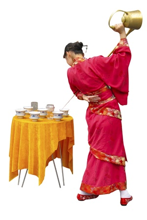 A Chinese girl in traditional dress pours tea into the cups photo