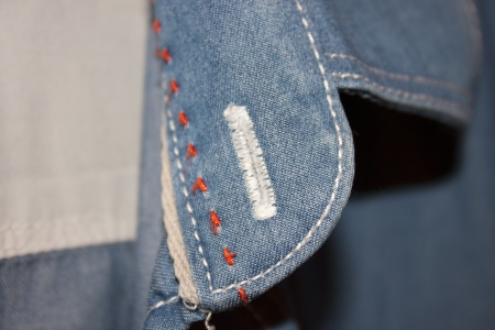 buttonhole: detail of a shirt in jeans with stitching and buttonhole