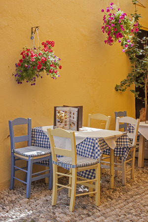 a typical Greek taverna with tables and straw chairs photo