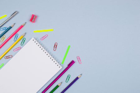 White notepad on a blue background, stationery-pencils, pens, paper clips, pencil sharpener are spread around. 版權商用圖片